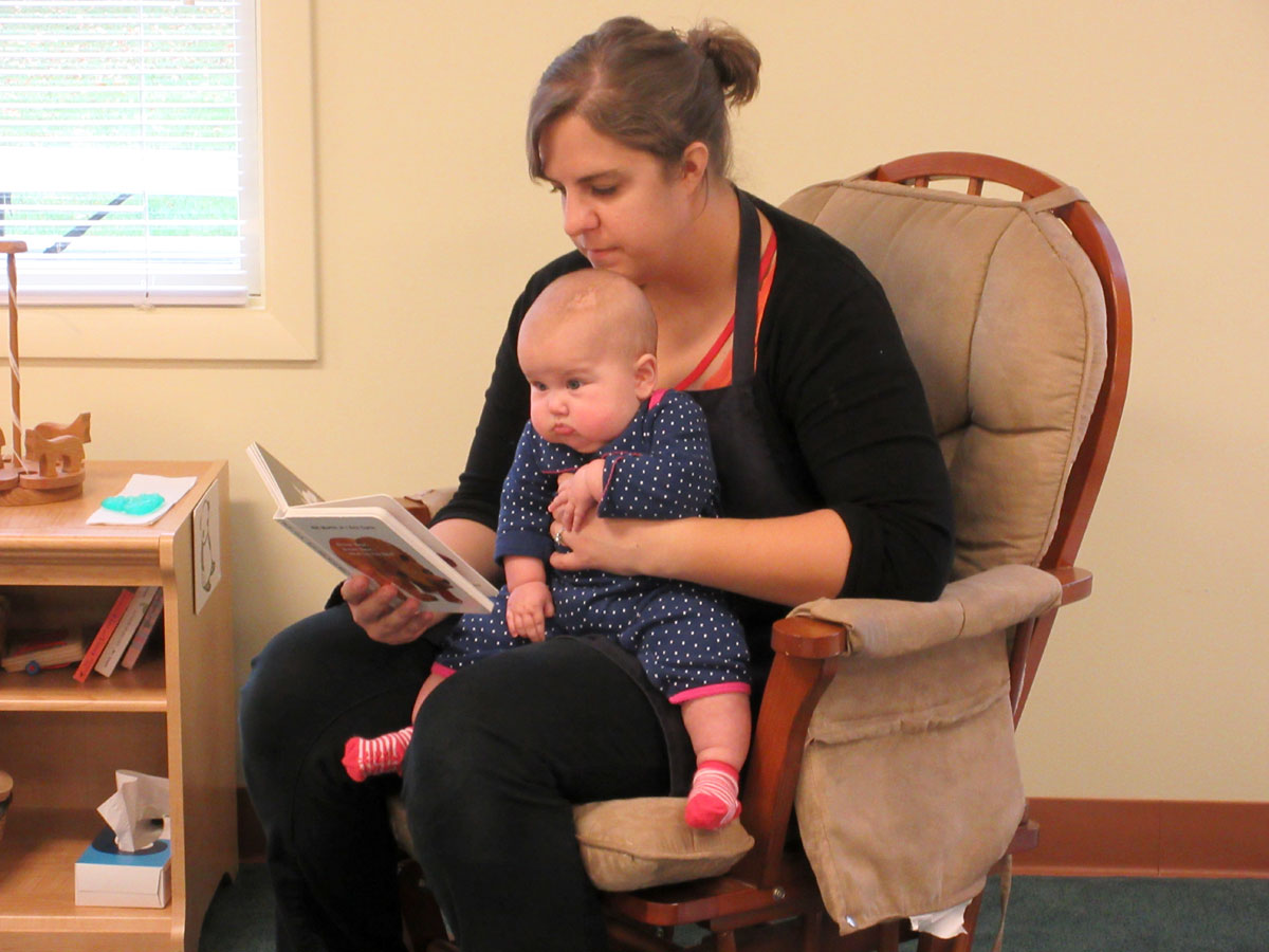 Teacher reading to baby in Nido