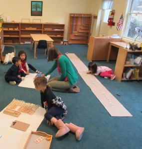 Children's House students working at rugs