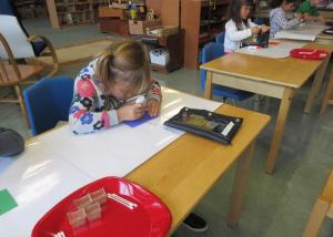 Children's House student concentrating on glue work