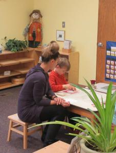 Children's House teacher working with a student