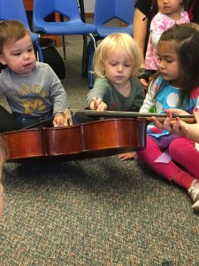 Young children exploring a cello