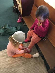 One young child helps another put shoes on