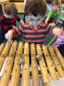 Young child playing wooden xylophone