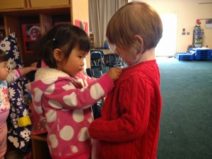Young children helping each other put on coats